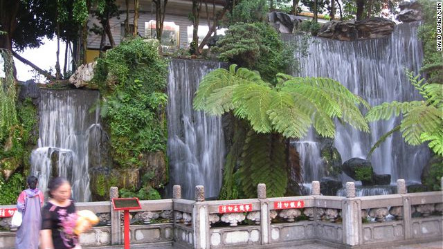 A waterfall welcomes visitors inside the first gate.