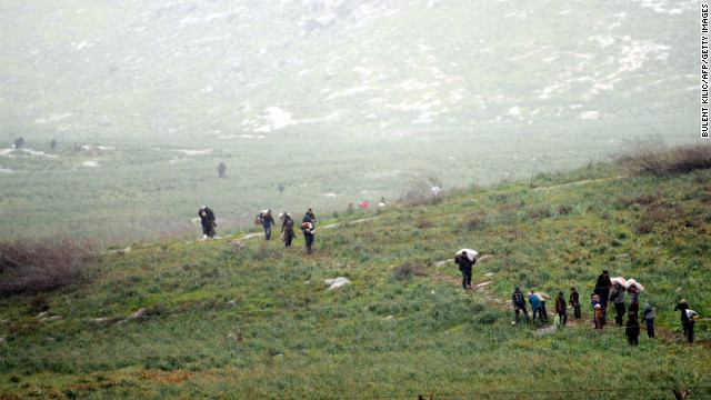 Syrian refugees walk across a field before crossing into Turkey on March 14, 2012. International mediator Kofi Annan called for an immediate halt to the killing of civilians in Syria as he arrived in Turkey for talks on the crisis.