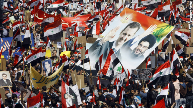 Thousands of Syrians wave their national flag and hold portraits of President Bashar al-Assad and Lebanon's Hezbollah chief Hassan Nasrallah, right, during a rally to show support for their leader on March 29 in Damascus.