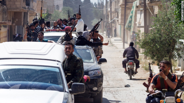 Members of the Free Syrian Army return to Qusayr on May 12 after an attack on Syrian regime forces in the village of Nizareer, near the Lebanese border in Homs.