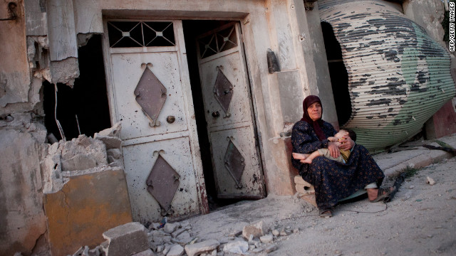 A Syrian woman sits with her grandson outside a damaged building after attacks in the Syrian village of Treimsa on July 13. More than 200 people were massacred in the town, according to activists.