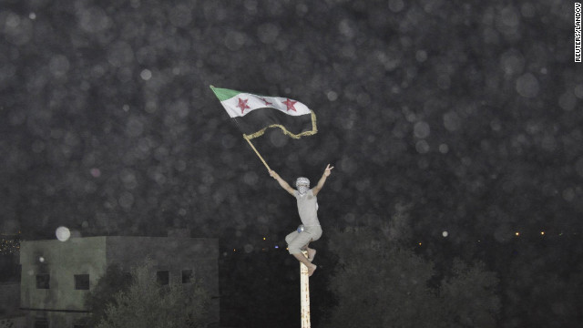 A Syrian demonstrator holds an opposition flag during a protest in Damascus on July 2. There have been increasing reports of violence in the Syrian capital.