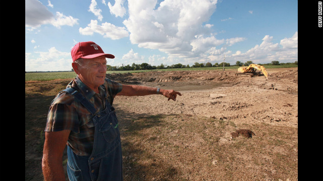 Farmer Marion Kujawa looks over a dried-up pond where his cattle used to water, near Ashley, Illinois, on July 16. Kujawa is digging the pond deeper so that the water will last longer in the future.