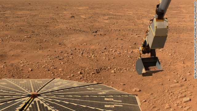 Phoenix's robotic arm scoops up a sample on June 10, 2008, the 16th Martian day after landing. The lander's solar panel is seen in the lower left.