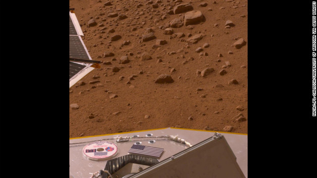 A U.S. flag and a DVD containing a message for future explorers of Mars, science fiction stories and art about the planet, and the names of 250,000 people sit on the deck of Phoenix in 2008.