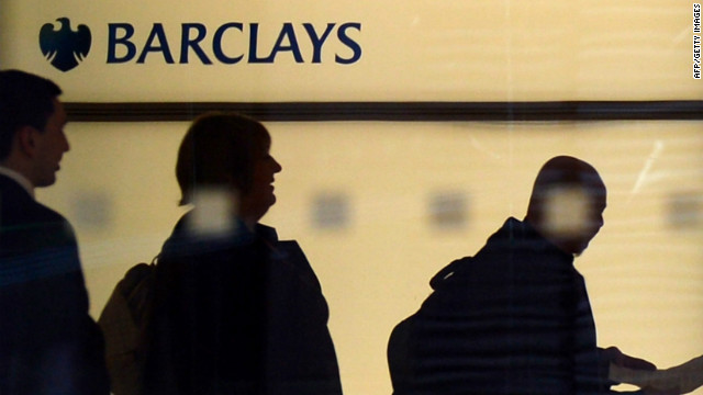 People walk past a Barclays logo at the bank's headquarters in Canary Wharf in east London, on July 3, 2012.