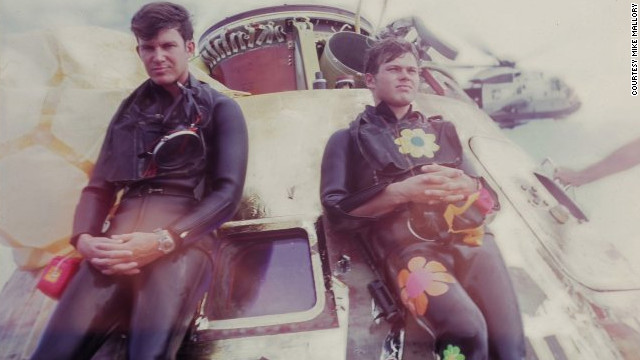 "Navy SEALs Wes Chesser, left, and John Wolfram pause after securing the Apollo 11 capsule on July 24, 1969. Wolfram wore 60s ""Flower Power"" decals, showing his rebellious side. Chesser says, that only now does he realize how physically demanding the mission was. ""We were in such good shape."""