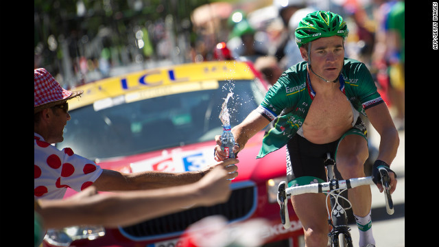 Stage winner Thomas Voeckler of France grabs a bottle of water from a fan as he climbs the final pass before the finish Wednesday, July 18, during the 197-kilometer (122-mile) race through the Pyrenees from Pau to Bagnres-de-Luchon. 