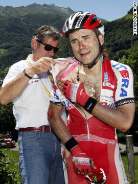 Katusha team rider Vladimir Gusev of Russia receives assistance from a race official after a fall in the Pyrenees on Wednesday.