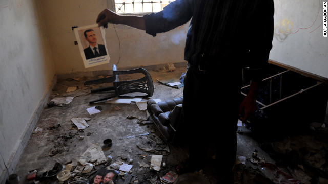 A man holds up a picture of President Bashar al-Assad at a former police station in Atareb after clashes between Syrian soldiers and Free Syrain Army near Aleppo on Thursday, July 19. Rebels seized control of border crossings with Iraq on Thursday, dealing a new blow to al-Assad, as China and Russia dismayed the West by blocking U.N. action against his regime.