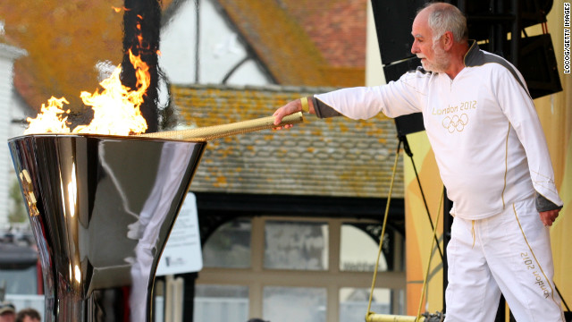 Keith Leech of Hastings uses the Olympic flame to light the cauldron in Hastings on Tuesday, July 17.