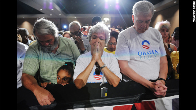 Obama supporters observe a moment of silence for the victims of the Aurora, Colorado, shootings at a campaign event at Harborside Event Center in Fort Myers, Florida, on Friday, July 20.