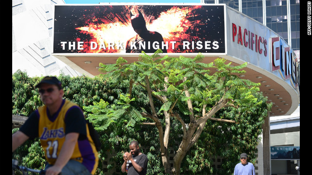"A cyclist and pedestrians pass a theater showing the latest Batman movie in Hollywood, California, on Friday. Warner Brothers said it was ""deeply saddened"" by Friday's massacre at a Colorado screening of ""The Dark Knight Rises."""