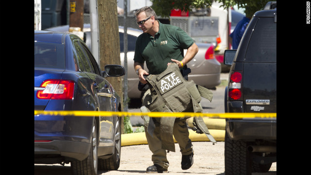 A Federal ATF officer carries protective gear onsite at the home of alleged shooting suspect James Holmes.