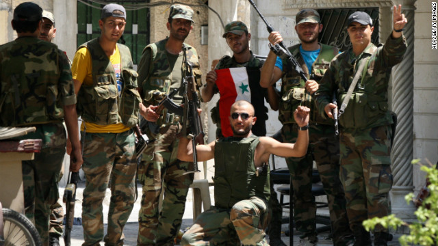 Members of Syria security forces pose for photographers in the al-Midan area in Damascus after driving out the rebel fighters.