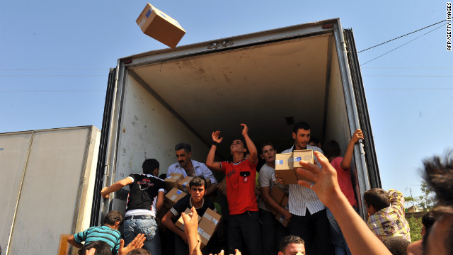 Syrian residents take goods from a truck that rebels captured at the Bab al-Hawa border crossing with Turkey on Friday.