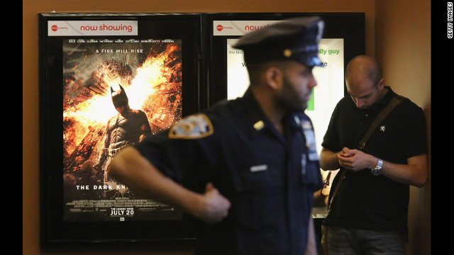 "An NYPD officer keeps watch inside an AMC move theater where the film ""The Dark Knight Rises"" is playing in Times Square on Friday. NYPD is maintaining security around city movie theaters following the deadly rampage in Aurora, Colorado."