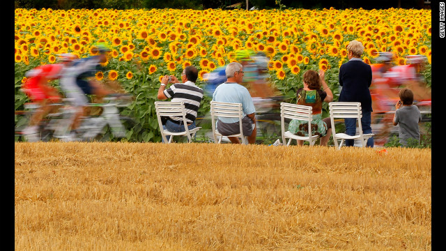 Fans watch as the peloton passes through sunflower fields on Friday.
