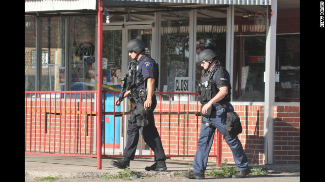 Members of the Aurora Police Department SWAT unit walk near the apartment of James Holmes. Police have Holmes, 24, of North Aurora, in custody.