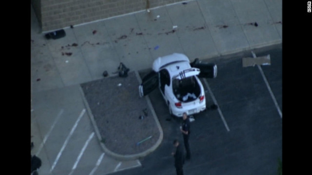 What is believed to be the suspect's car is examined after the shooting.