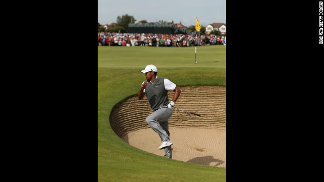 Woods scrambles out of a greenside bunker after hitting the ball close on fifth hole.