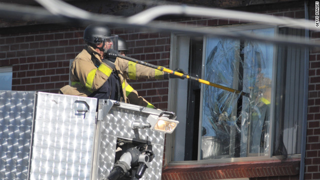 Police break a window at the suspect's apartment Friday in Aurora.