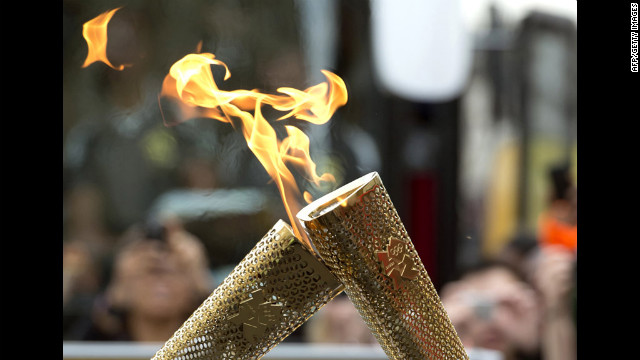 Torchbearers &quot;kiss&quot; their torches to pass the Olympic flame during the London 2012 torch relay through the Borough of Tower Hamlets in London on Saturday, July 21.