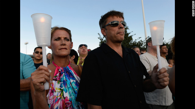 Alicia Prevette, left, and Paul Stepherson attend a vigil for the victims Friday at the Century 16 movie theater. 