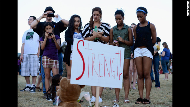 A group of teenagers stand behind a sign that reads &quot;Strength.&quot; 