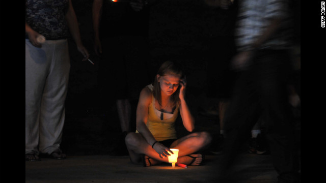 A woman holds a lit candle at a makeshift memorial.