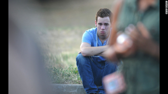 A mourner grieves on the curb during a memorial service.