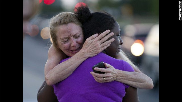 Two women mourn near the theater on Saturday.
