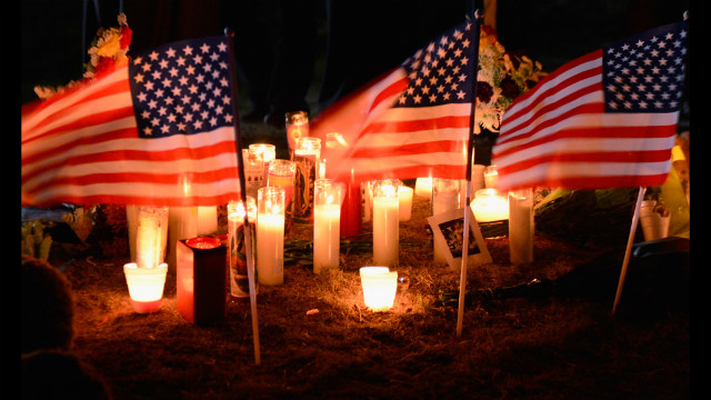 Flags, flowers and candles make up a memorial site.