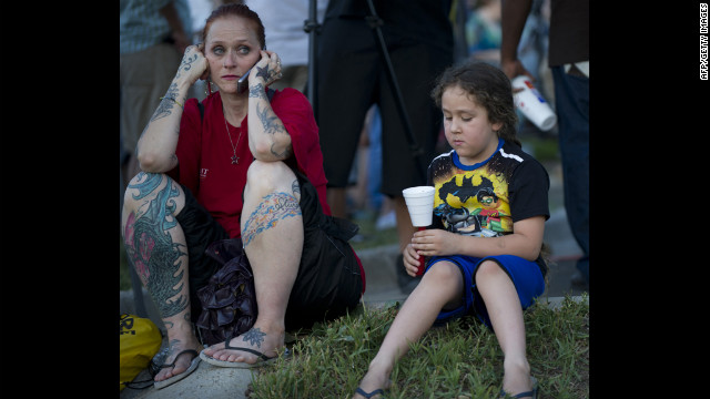 Two mourners sit on the ground at a vigil. 