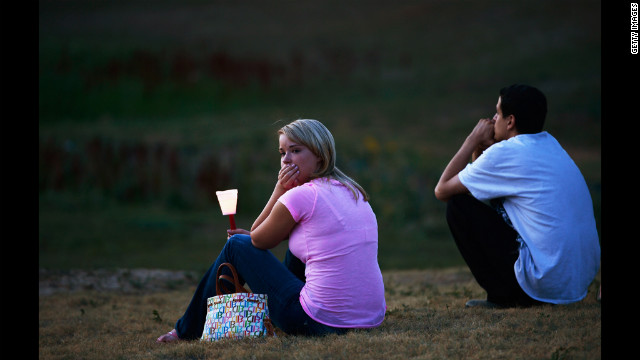 A woman looks at a makeshift memorial after attending a candlelight vigil.