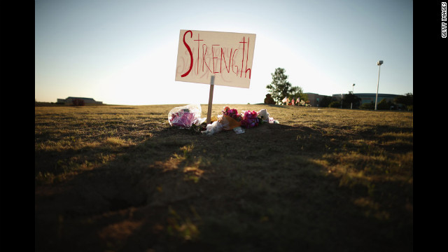 Handwritten signs decorate the makeshift memorial across from the Century 16 movie theater on Saturday.