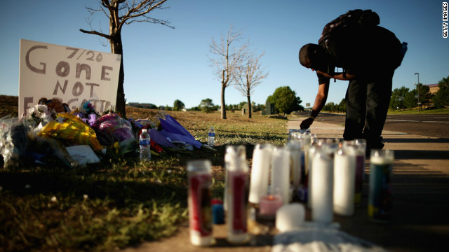 Gerald Wright, 24, relights candles that have blown out at the victims' memorial across from the movie theater.