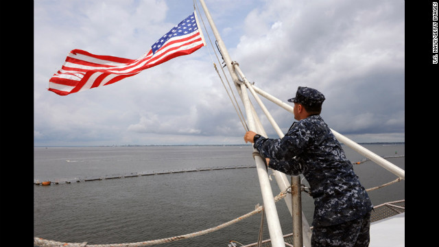 Aviation Boatswain's Mate 3rd Class Jajuan Mangual lowers the American flag on the flight deck of the aircraft carrier USS George H.W. Bush to half-mast on Saturday. One U.S. Navy sailor was killed in the shooting and another injured.