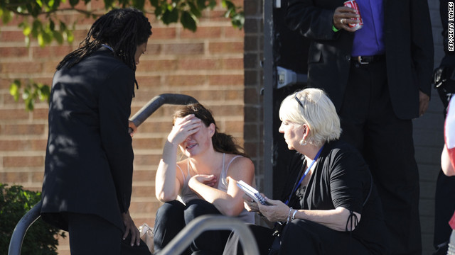 A distraught woman receives counseling from Pastor Quincy Shannon, left, in front of Gateway High School in Aurora, where the families of the missing met following the shooting.