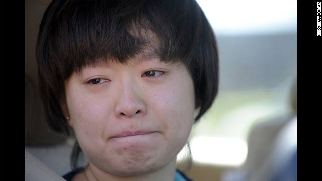 Lin Gan of Aurora holds back tears as she speaks to reporters about her experience in the Century 16 theater Friday.