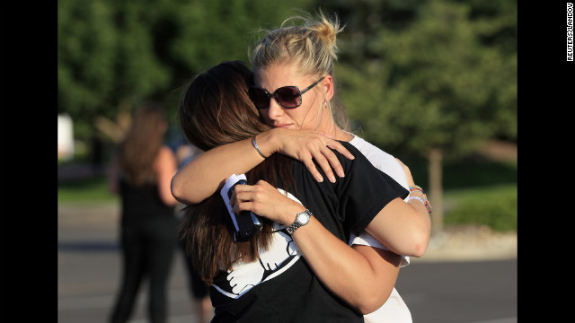 People embrace before a vigil for victims behind the theater where a gunman opened fire on moviegoers.