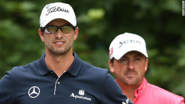 Overall leader Scott, left, waits with McDowell on the first tee during the final round of play.
