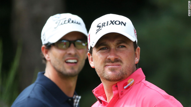 Graeme McDowell of Northern Ireland watches his tee shot on the second hole as Scott looks on.