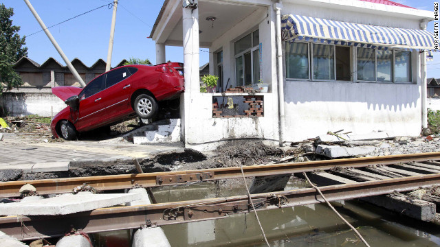 A flood-swept car is lodged against a building at a railway crossing in Beijing on Saturday, July 21.