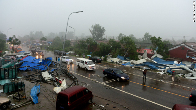 Commuters make their way home through roadside debris as a storm hits Beijing, July 21.