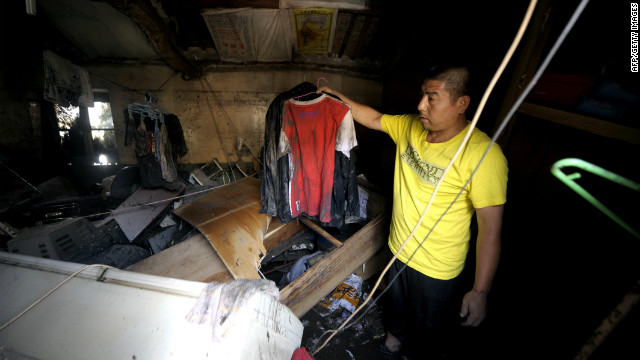 A resident checks his damaged home after a storm hit the city, July 22.