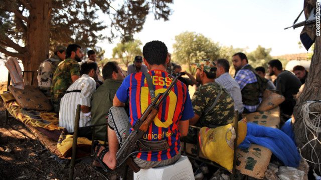 An armed Syrian rebel wearing the jersey of FC Barcelona rests with comrades near the northern city of Aleppo on Sunday. The rebel Free Syrian Army announced the start of the battle to 