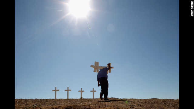 Greg Zanis of Aurora, Illinois, carries two of the 12 crosses he made for a makeshift memorial to the victims of last weekend's mass shooting at the Century 16 movie theater on Sunday, July 22.
