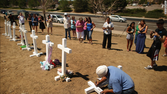 Greg Zanis writes the names of the victims of last weekend's mass shooting on the crosses before erecting them at the memorial across from the Century 16 movie theater on Sunday. Zanis, a carpenter, drove all night from Illinois to deliver the crosses.