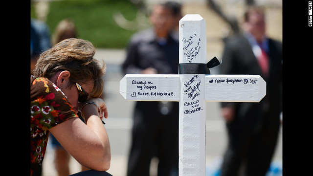 Angie Terry of Alabama prays next to a white wooden cross erected for victims.